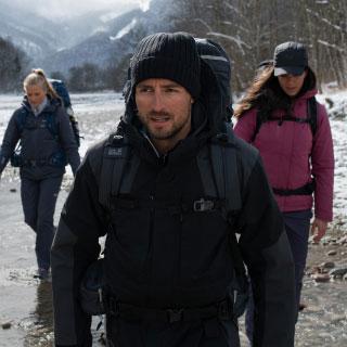 Drei Wanderer laufen durch einen Fluss